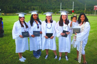 2010 Hoopa Valley High School graduates and cousins (left to right) Lori Baldy, Ariel Richards, Loni Blady, Shirley Hurley, and Athena Markussen holding daughter Waysey Reed after the commencement excercises. / Photo by Manuel Sanchez, Two Rivers Tribune.