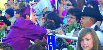 Hoopa Valley High School graduate Shahn Colegrove-Perry gets emotional while handing his grandparents a rose during the 2010 HVHS graduation on June 11 at Pritchard Field. / Photo by Manuel Sanchez, Two Rivers Tribune.
