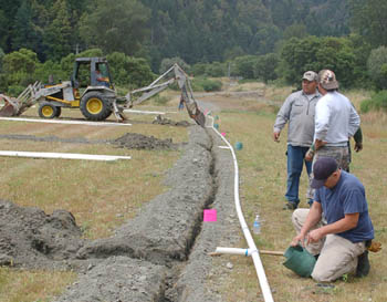 Volunteer Aaron Pole works on the water line, while crew leader Lonnie Wilson goes over plans with a parent volunteer. The 40 volunteers installed over 1,000 feet of irrigation line for the new field. / Photo by Manuel Sanchez, Two Rivers Tribune.