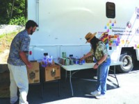 Department of Health and Human Services staffer Doug Moyer (left) and Martha Meade prepare to distribute food in Weitchpec. Countywide, more than 300 boxes of food have been distributed with another 200 possible by Sept. 30. / Photo courtesy of Leslie Lollich.