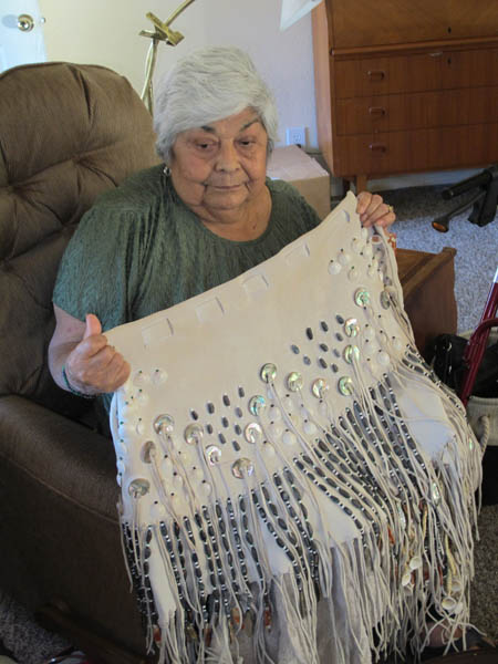 "Laverne Glaze, the elder basket weaver and Karuk activist, shows off a regalia skirt still a work in progress. She reflected, ""My life is getting pretty damn short I still need to teach some of these young girls how to sew dresses.""/Photo by Malcolm Terence"