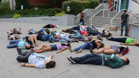 Youth protestors lay on the ground in front of the Klamath County Government Office, representing the image of past fish kills on the Klamath river largely due to contamination and low flows./Photo courtesy of Youth Coalition for Clean Klamath.