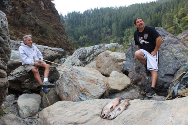 Ron Reed, right, explains his views on the losses of Karuk ecological knowledge and the efforts to rebuild it, between passes of dipnet fishing at Ishi Pishi Falls. His companion Brian Tripp, adds his own perspective./Photo by Jayme Kalal.