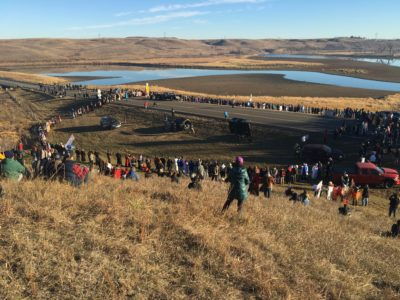 A crowd of water protectors form a prayer circle as part of an action at Standing Rock. Their campaign to stop the construction of a pipeline that could threaten Sioux tribal water supplies has drawn thousands of supporters to North Dakota and members from at least 300 tribes. Their tactics, all non-violent, have been met with increasing violence by heavily militarized police./Photo by Aja Conrad.
