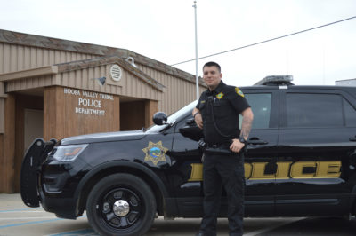 Hoopa Tribal Police Officer, Robert Buckman stands next to his patrol vehicle. Buckman graduated from College of the Redwoods Police Academy in 2015./Photo by Rhonda Bigovich, Two Rivers Tribune Contributor.