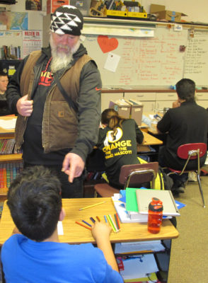Ben Saxon, standing, praises the work of a student at Junction School in Orleans. He was part of a team that shared traditional stories with students in local schools./Photo by Malcolm Terence, Two Rivers Tribune Contributor.