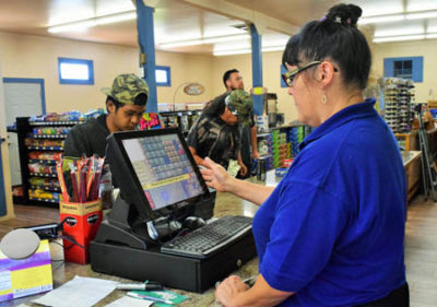 Store manager Anjelique Blake stands in front of the new point-of-sale system at the Weitchpec grocery store. The new system will catalog inventory in a better, more efficient way./Photo by Molli Myers, Two Rivers Tribune.